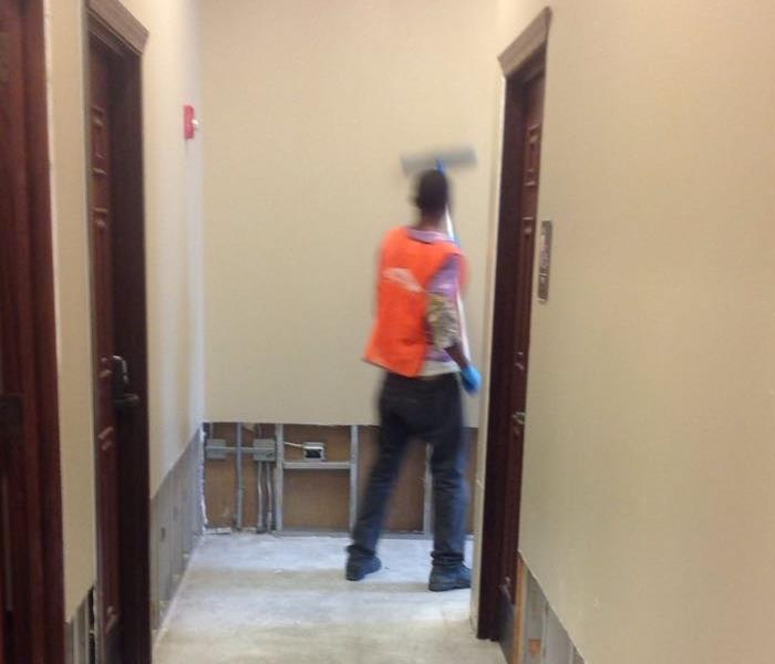 SERVPRO team member in orange vest cleans walls in the hallway of a commercial building.