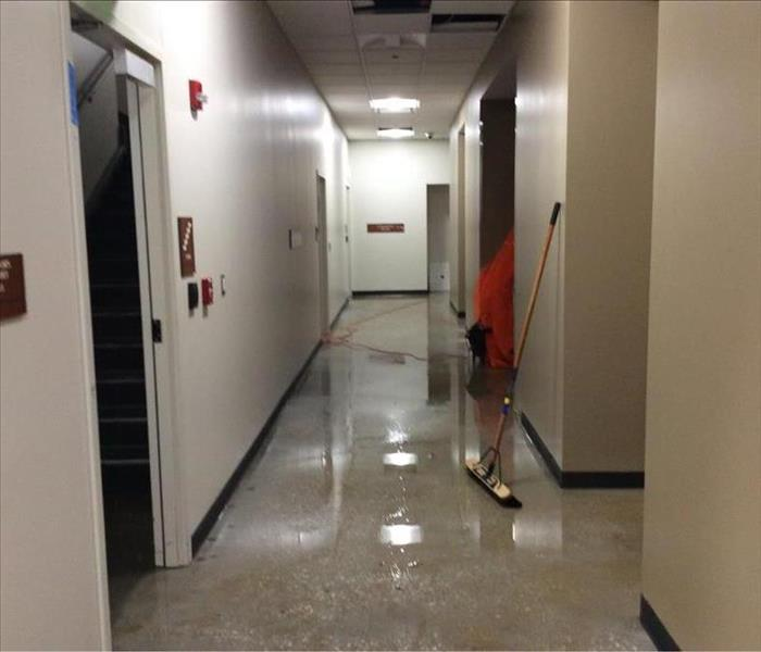Commercial hallway with pools of water after a loss.