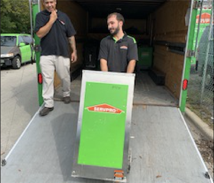 Two SERVPRO members loading the truck with equipment.