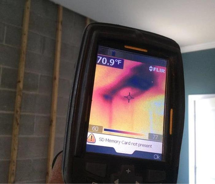 Thermal camera in action pointed towards a ceiling showing a dark spot where water is hidden.