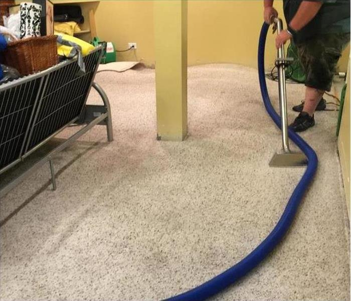 Someone extracting water from a carpet in a home